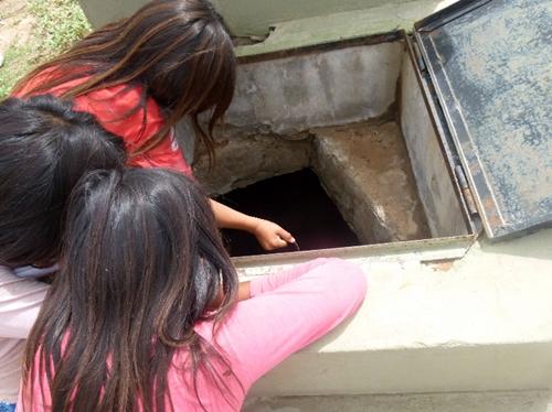 Niñas tomando agua con un balde de un pozo contaminado