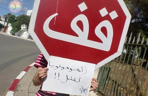 Un joven coloca un cartel bajo una señal de