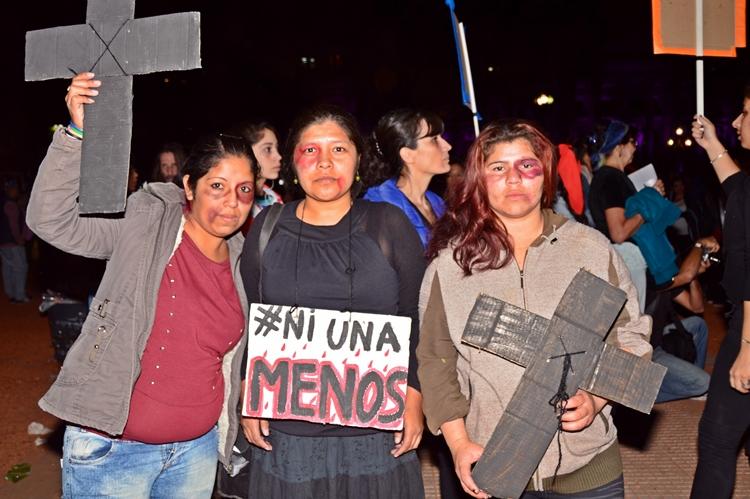 Uan mujer muestra las marcas de la violencia de género en su cara, y sus dos compañeras se solidarizaron con ella pintándose moretones