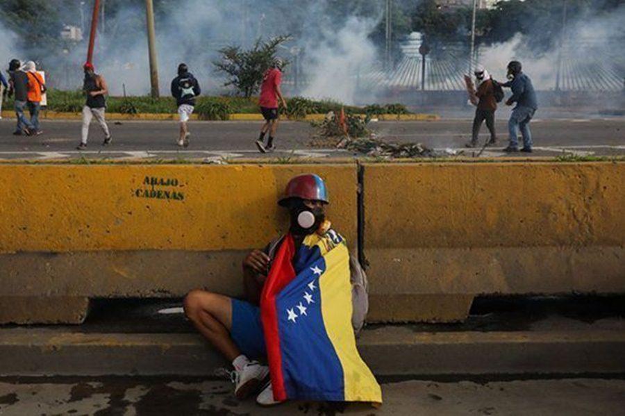 un-manifestante-se-protege-detras-de-un-muro-durante-las-protestas.-efe-violencia-venezuela-oposicion-bandera-580x386.jpg